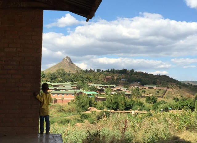 Small child standing with his back to the camera, looking out to a village with a hill in the background